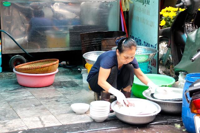Lavando louça na rua no Vietnã