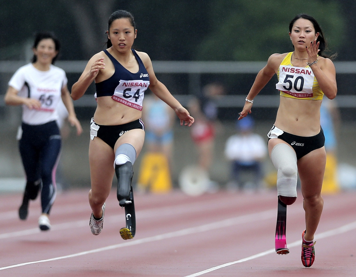In this photo taken Saturday, July 7, 2012, Paralympic athlete Maya Nakanishi, right, wearing new custom-designed, black and red racing blade, competes with Saki Takakuwa in the women's 100-meter final at the 17th Handicapped Truck and Field Championships in Tokyo.