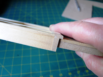 Hand holding up a piece of dolls' house kit wall, with the edge to the camera showing how there is space to add siding  and have room against the door frame.