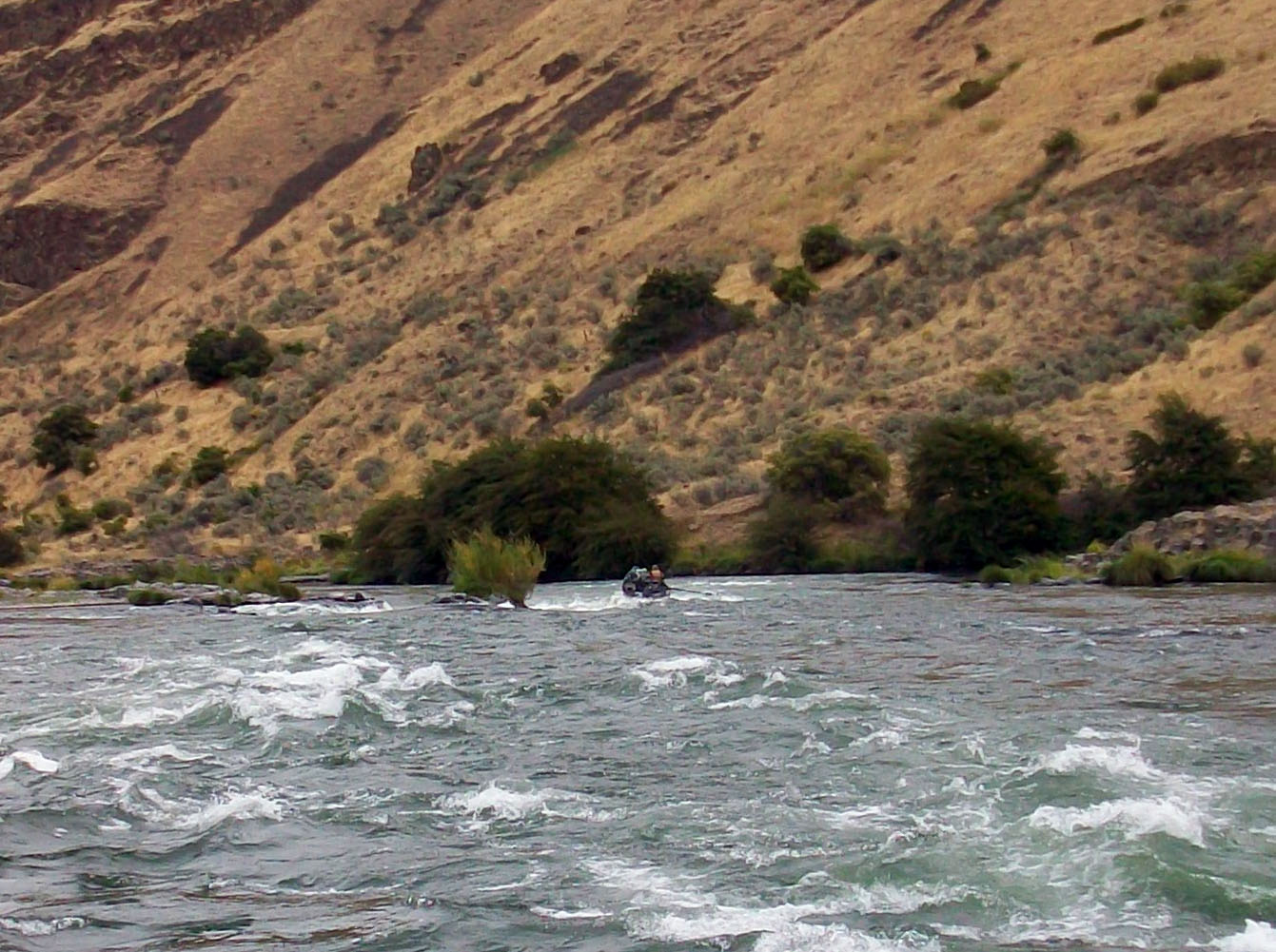 Picture of a drift boat floating the Deschutes River Canyon with the high desert hillside.in the background.
