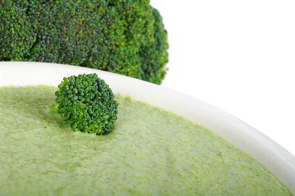 Een kom broccolisoep, geïnspireerd op een recept van Piet Huysentruyt met kaas in de soep verwerkt, met broccoli op de achtergrond