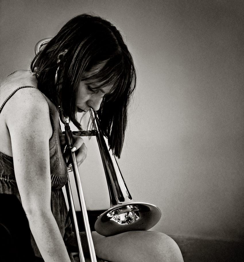 Retrato da artista numa pausa do concerto, com o trompote pousado na perna