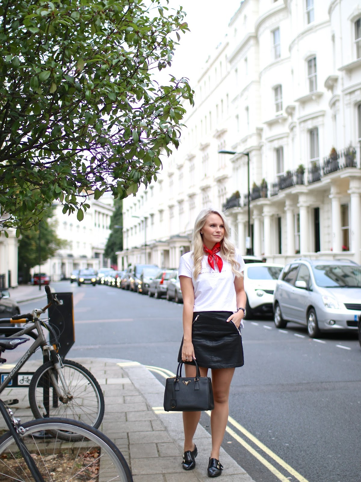 a blogger stands in front of a white building in the UK, demonstrating how to style a vintage bandana
