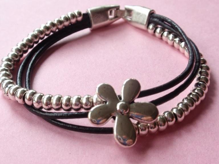Pulsera en cuero negro con flor plateada pequeña