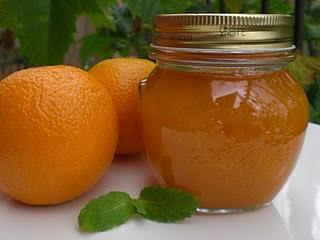 Frasco con mermelada y dos naranjas sobre mesa