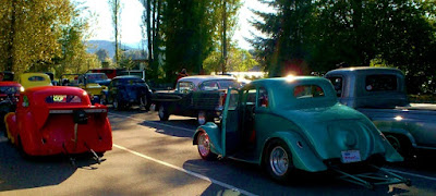 Colorful antique hot rods line up approaching the racetrack