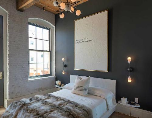 Vor Der Schwarzen Wand Steht Ein Bett Mit Felldecke, Auf Boden Liegt Ein  Heller Teppich