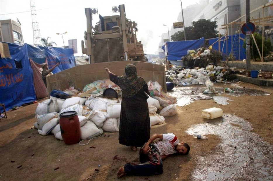 35 moments of violence that brought out incredible human compassion - woman defends a wounded protester from a military bulldozer