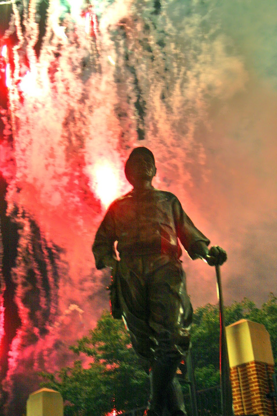Fireworks display behind statue of The Babe, baseball's greatest  hero.