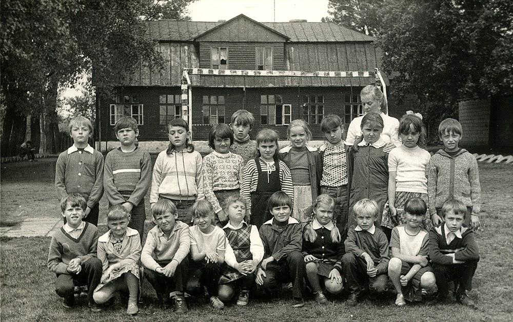 """Rogów rok 1986. Grupa dzieci wraz z nauczycielką - z tyłu """"stara"""", jeszcze istniejąca szkoła. Foto. z kroniki szkolnej."""
