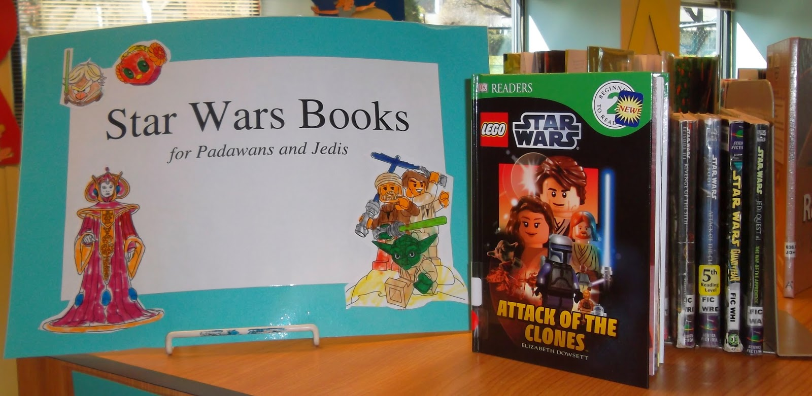 "Star Wars beginning readers' books propped facing forward with additional books shelved between bookends. To the left, a sign proclaims ""Star Wars Books for Padawans and Jedis."" The sign is decorated with cut-out characters from Angry Birds Star Wars and Lego Star Wars"