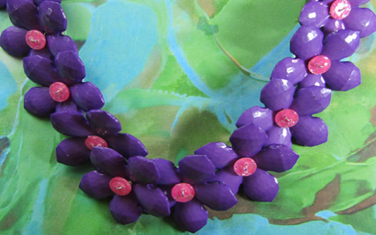 Big fashion necklace with linked bold purple and pink flower buttons