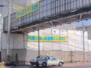 写真:「がんばろう仙台」「地震に強い歩道橋にします」の看板を掲げた工事中の歩道橋