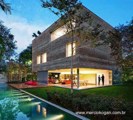 Vista nocturna de la Casa Cubo desde el jardín y la piscina