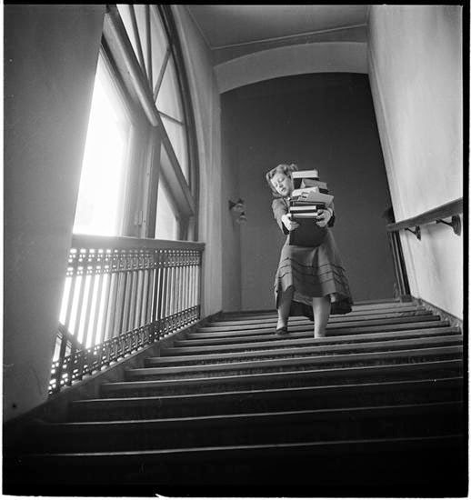 Columbia University, Student carrying a stack of books down stairs.