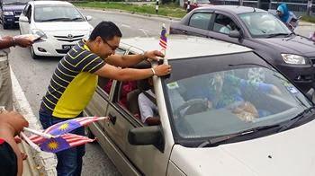 Mengedar bendera sempena hari merdeka kepada pengguna jalan raya sekitar simpang 4