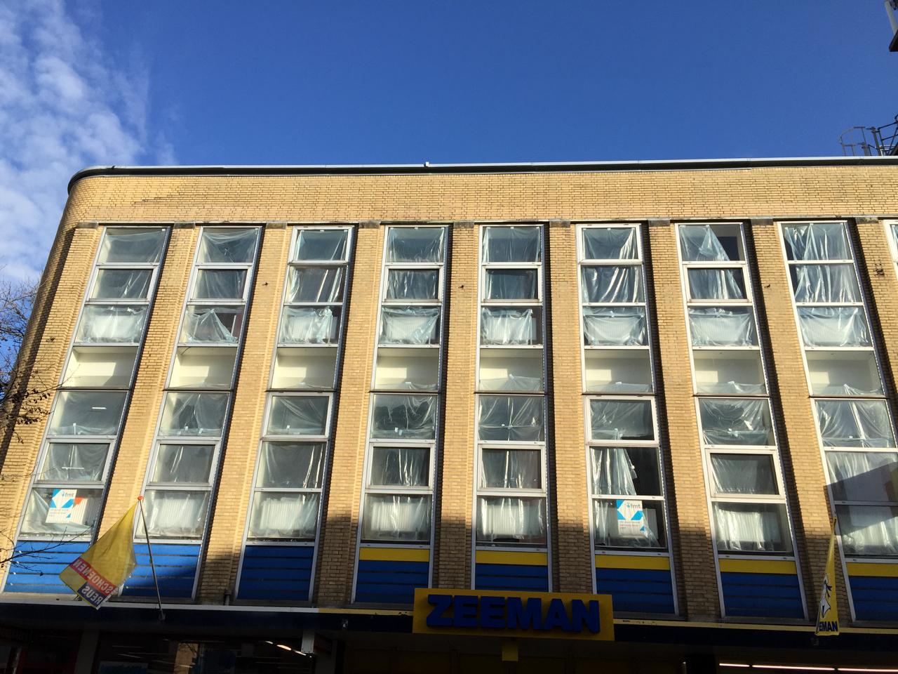 Leegstaande verdiepingen met gescheurd plastic voor de ramen