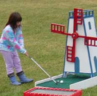 Young girl playing a windmill shot on a mini golf course