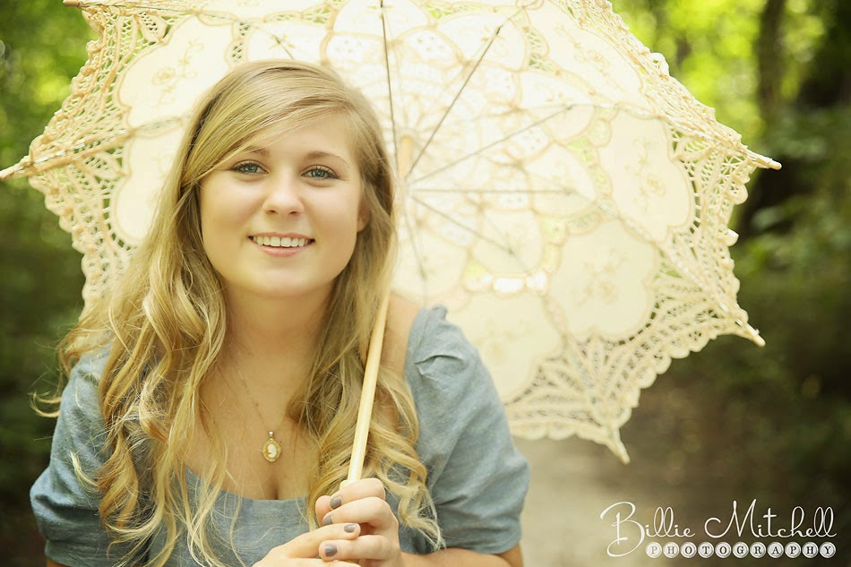 senior girl in grey dress holding cream color parasol in a park