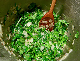 Greens Being Stirred and Cooked Down with Onion and Spices