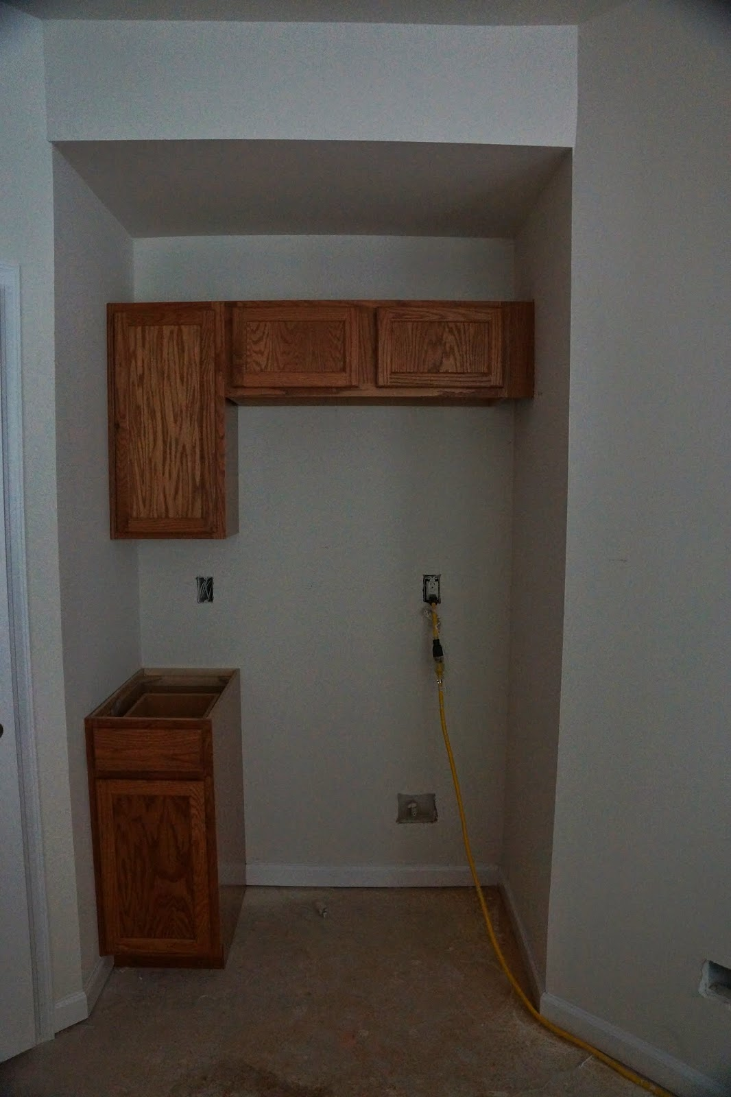 Picture of the kitchen cabinets around where the refridgerator will be before the counter is installed