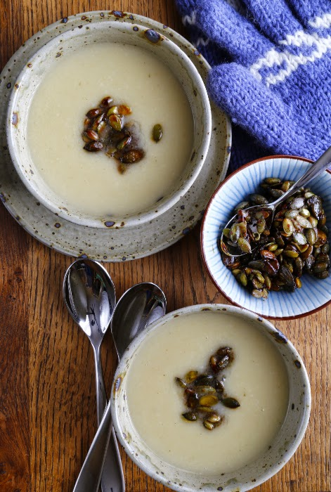 Two bowls of celeriac soup, a bowl of pumpkin seeds, spoons and gloves