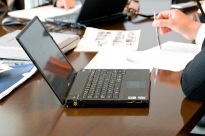 会社の会議でパソコンを開いている