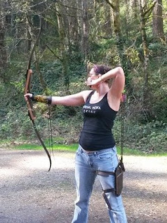 Image is a dark haired light medium skinned female presenting person with a black tank top, blue jeans, pigtail buns, and glasses. She's holding a bow and wearing a quiver on her thigh & an arm guard on the arm. The bow is empty because she just released; her right arm is out straight, holding the bow, and her left hand is still just in front of her left ear.