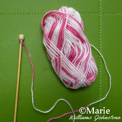 Variegated pink candy yarn wrapped around wooden knitting needle