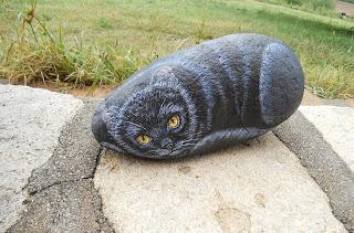 Piedra pintada con un gato negro.