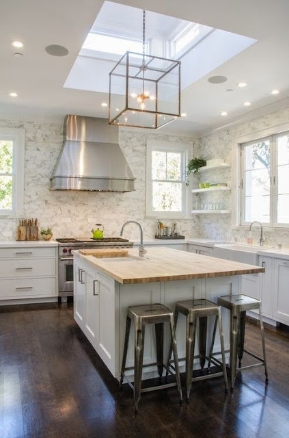 white kitchen with dark wood floors square gold glass pendant lights marble backsplash wood countertop