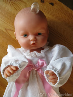 Close-up of baby doll, with curl on its forehead. Its sleeves come down to its knuckles.