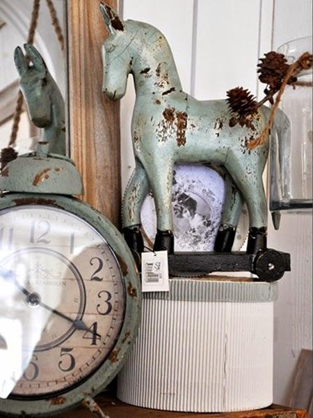Konik z drewna obok niebieskiego starego zegarka