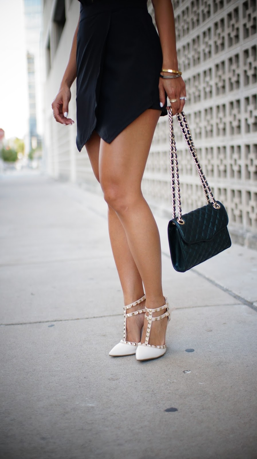 Backless Black Romper & Studded White Pumps outfit