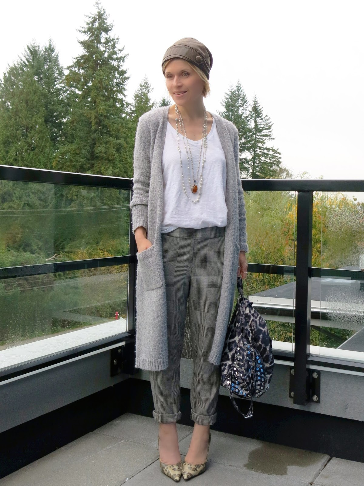 styling slouchy plaid pants and a white tee with layered necklaces, a long cardigan, leather beanie, and leopard-print pumps