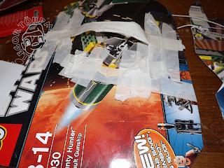 Szöveg: A pajzs hátoldala és a rögzítési mód. Kép: Star Wars-os doboz pajzs-formára vágva. Papírragasztócsíkkal van összetákolva a kéztartó része.
