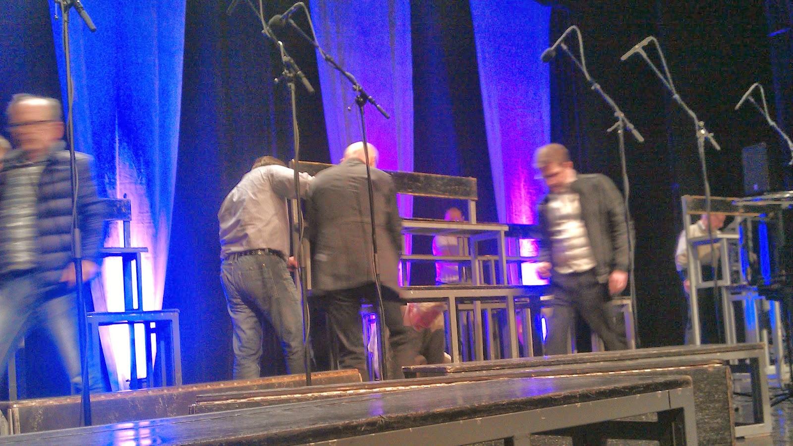 Basar och tenorer bygger ihop körpallarna på scenen i Vara konserthus. Foto: Karin Lönnå
