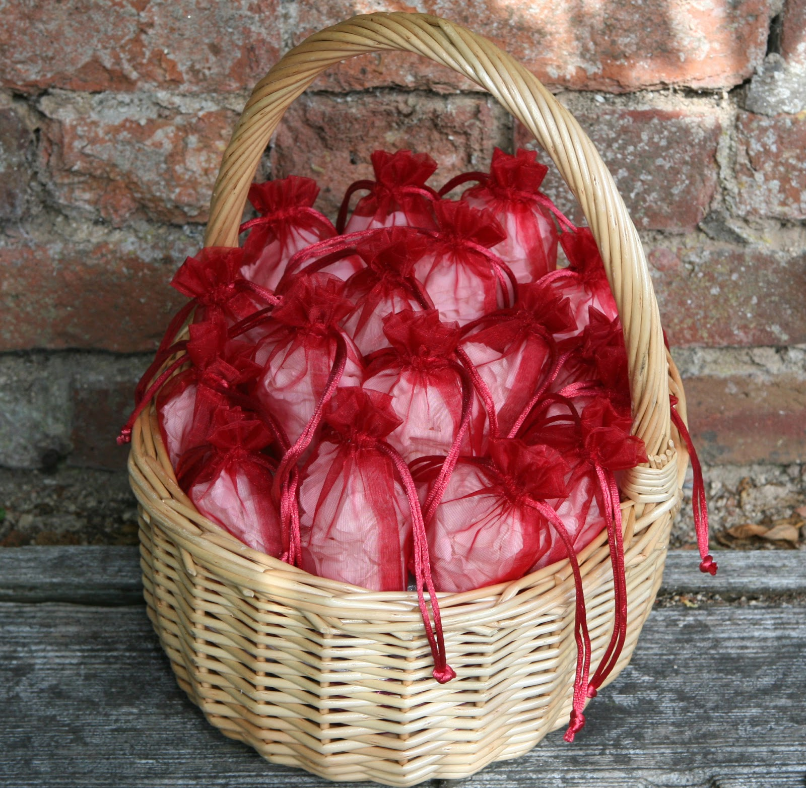 The confetti blog choosing your petal confetti tips advice red bags filled with white rose petals in a deep oval basket mightylinksfo