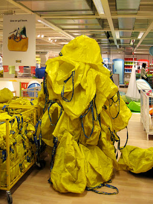 Photo: person hiding in IKEA with a suit of IKEA carry bags