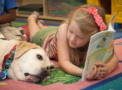 child reads to yellow Lab