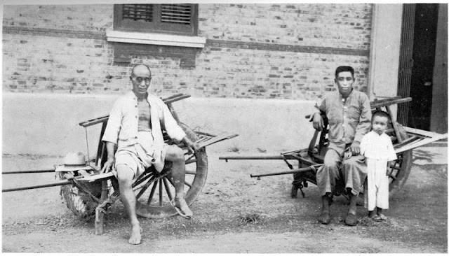 Chinese sitting on a wheelbarrow posing for a picture