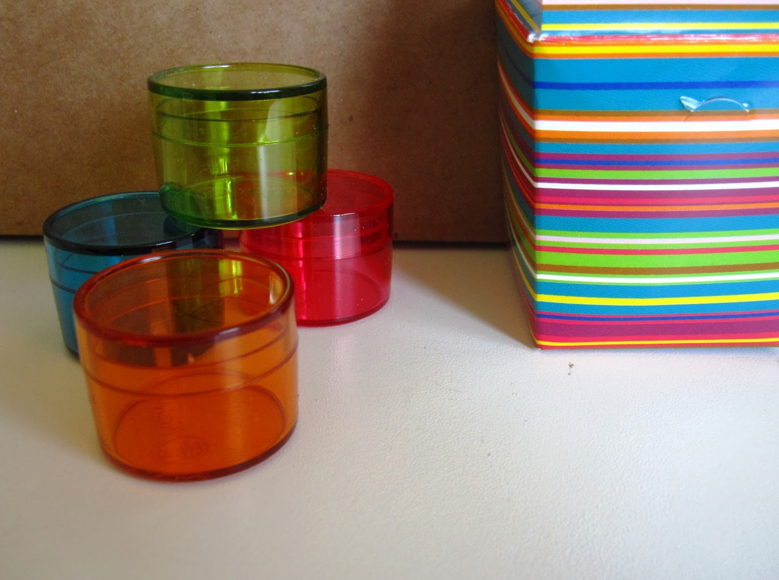Four small coloured see-through miniature storage containers