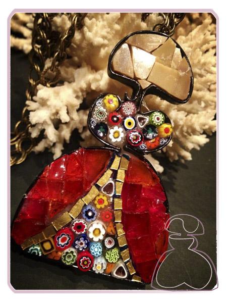 Colgante Menina de El Jardín del Edén por Sylvia López Morant decorada en minifioris, cristal de Murano y esmalte veneciano transparente montada sobre tono bronce.