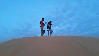 Two tourists on top of a sand dune in Muine, Vietnam