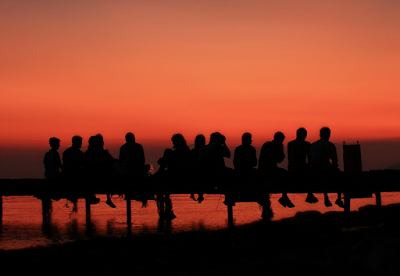 "Image of people sitting on dock titled ""Friends"" by Christos Loufopoulos (ophilos on flickr) Taken on August 18th, 2011 (CC-by-2.0)"