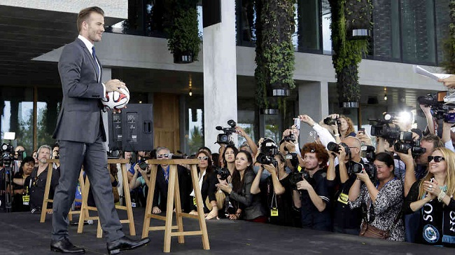 Former soccer star David Beckham holds a ball at a news conference where he announced he's exercising an option to buy a Major League Soccer expansion team in Miami. (photo: Lynne Sladky/AP)