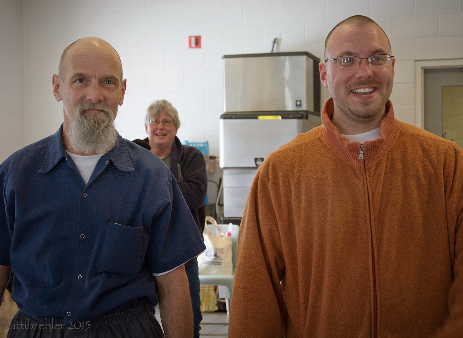 Two men are facing the camera, a woman is approaching from behind them just over the shoulder of the man on the left. The man on the left is wearing a blue short-sleeved shirt and is bald with a gray beard. The man on the right is wearing an oranged jacket and glasses. Both men are smiling.