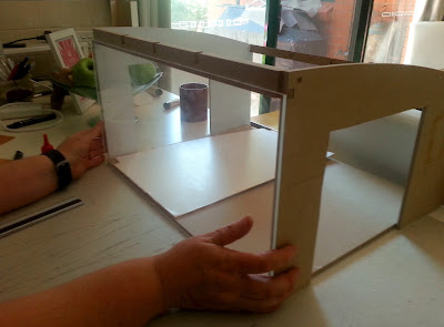 Holding a piece of cut perspex up against the front of a doll's house kit.