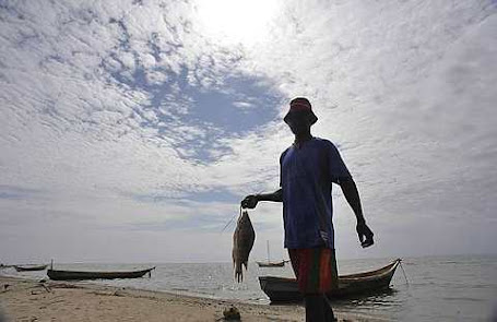 A fisherman carries a fish after a catch in Lake Turkana