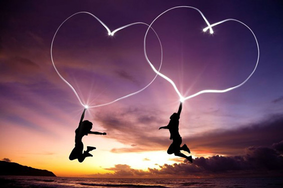 Couple jumping in air holding hearts made of light